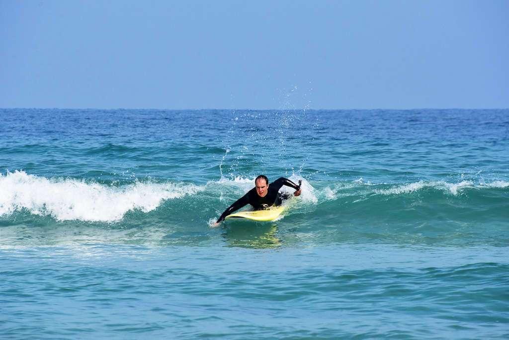 Remando para coger una ola en la playa de Razo