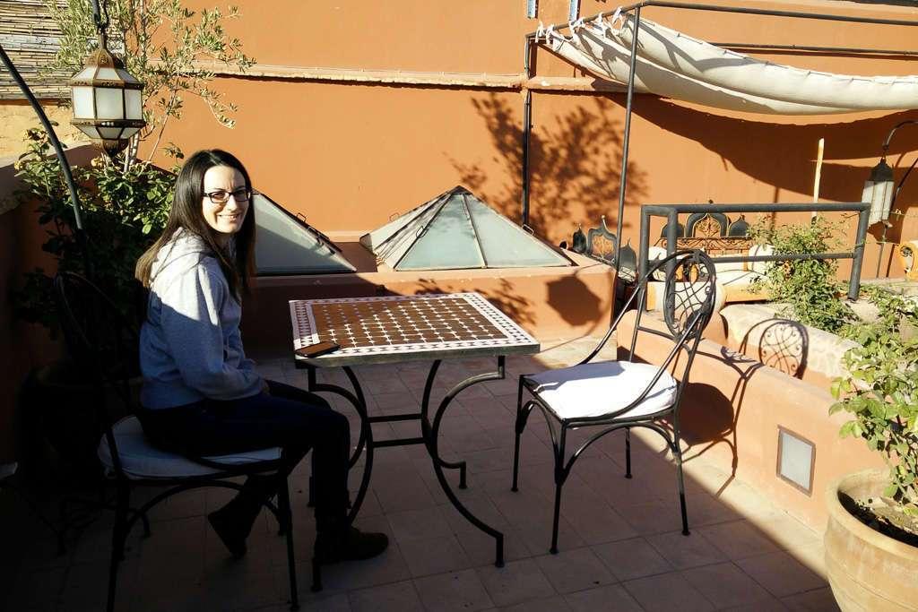 Lena sentada en la mesa de desayuno de la terraza del riad Dar Nakous en Marrakech