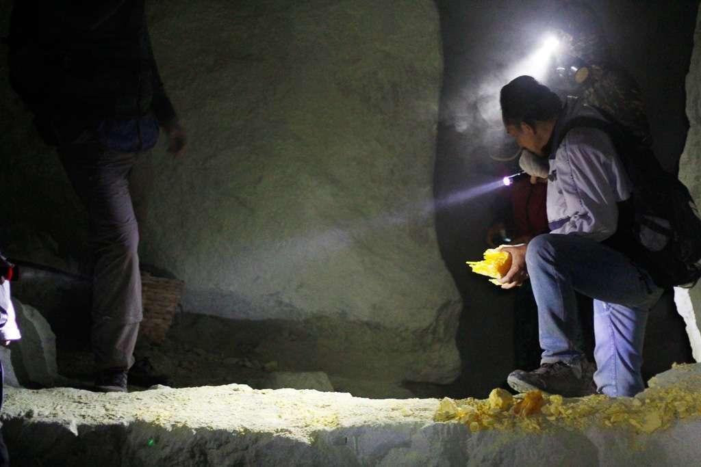 Una persona cogiendo un trozo de azufre en el volcán Ijen