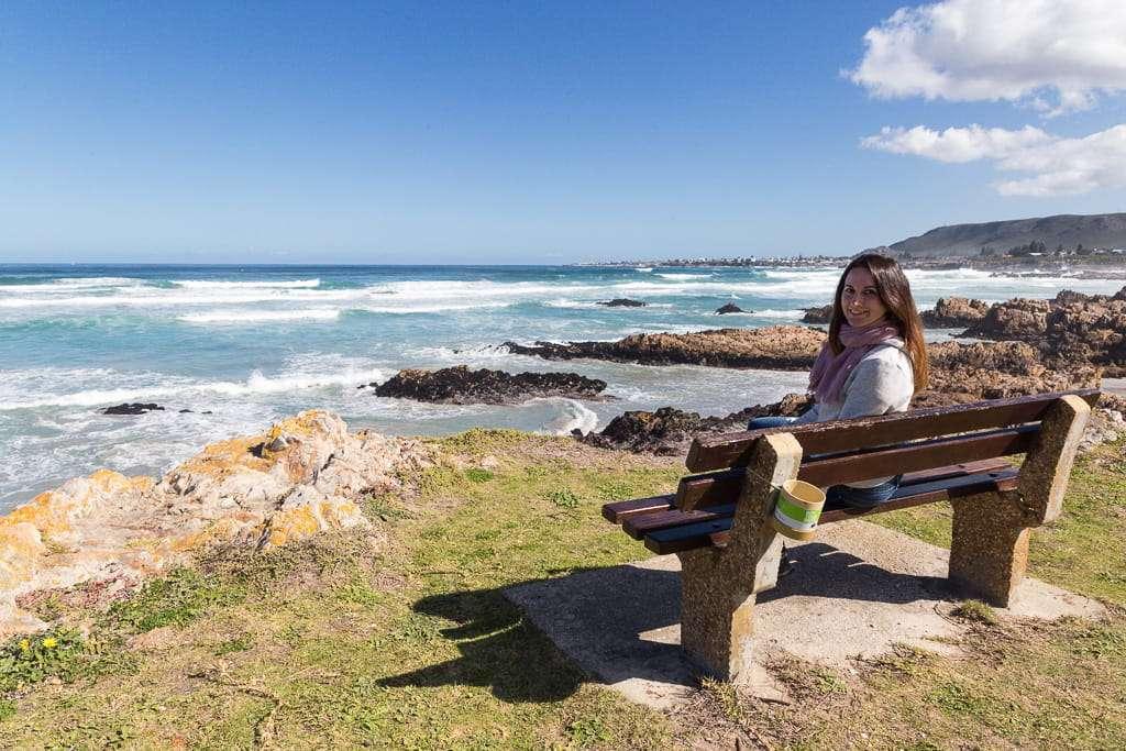 Lena en un banco del cliff path de Hermanus, Sudáfrica