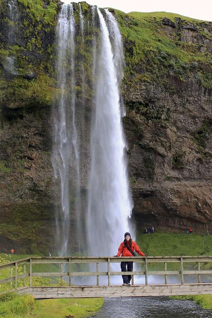 Lena frente a la cascada Seljalandsfoss en Islandia