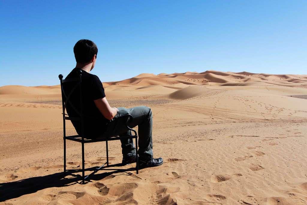 Alberto sentado en una silla en medio de las dunas