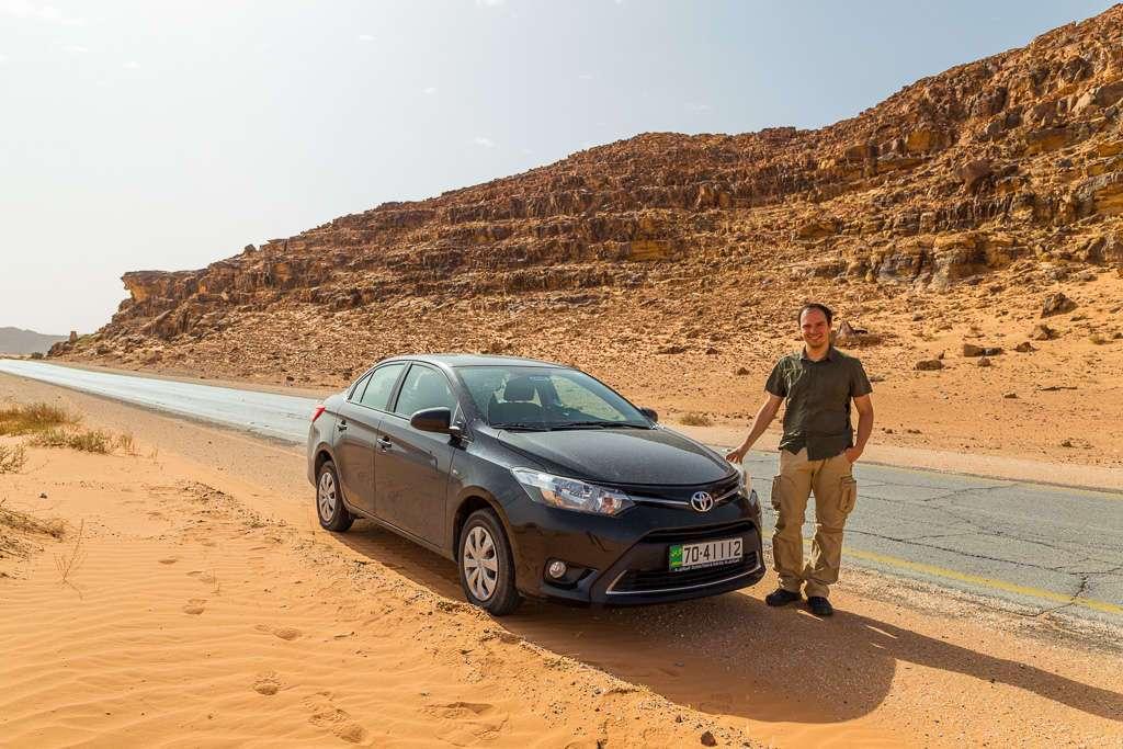 Alberto delante del coche en una carretera de Wadi Rum, Jordania