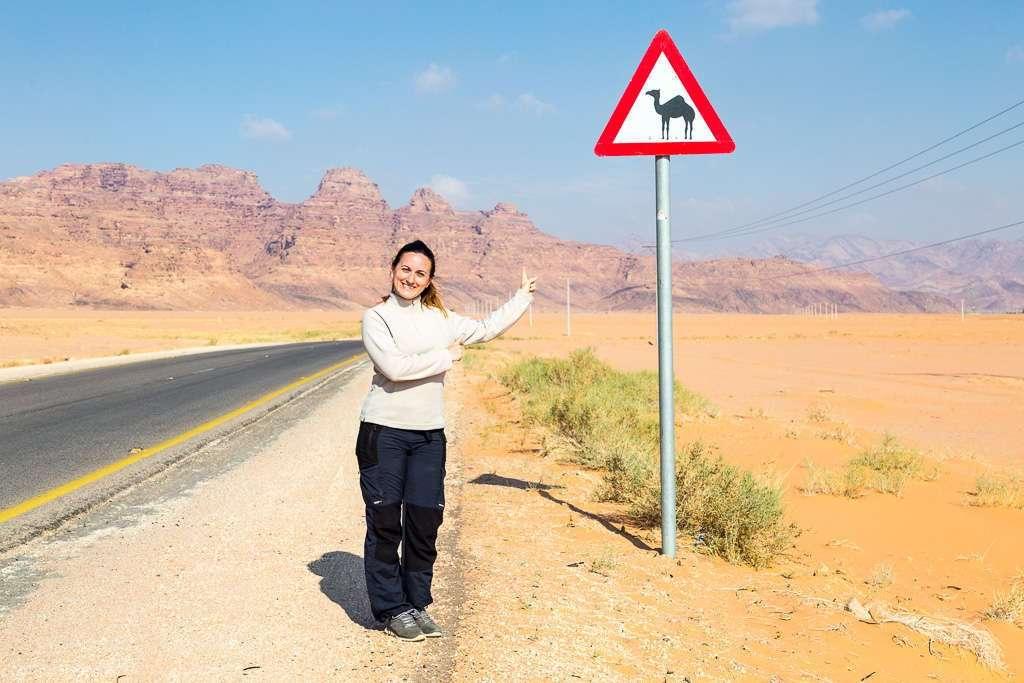 Lena frente a una señal de peligro camellos, Wadi Rum, Jorania