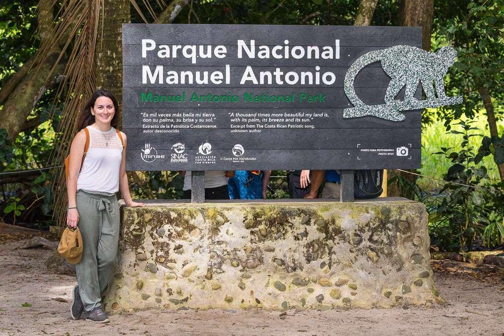 Lena delante del cartel del Parque Nacional Manuel Antonio, Costa Rica