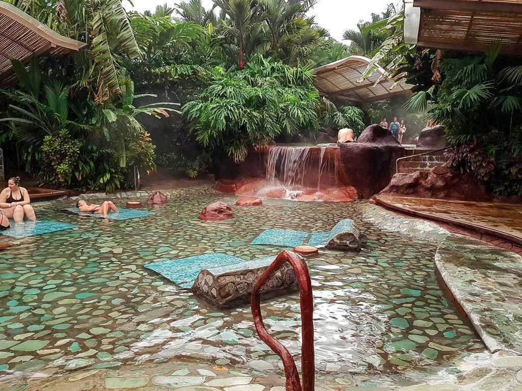 Piscina con tumbonas y cascada en las termas Baldi, Arenal, Costa Rica