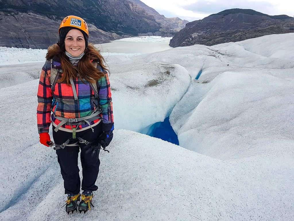 Lena delante de un agujero en la caminata sobre el hielo del glaciar Grey, Torres del Paine, Chile